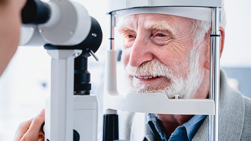 Optometrist checking older adult male's sight with slit lamp