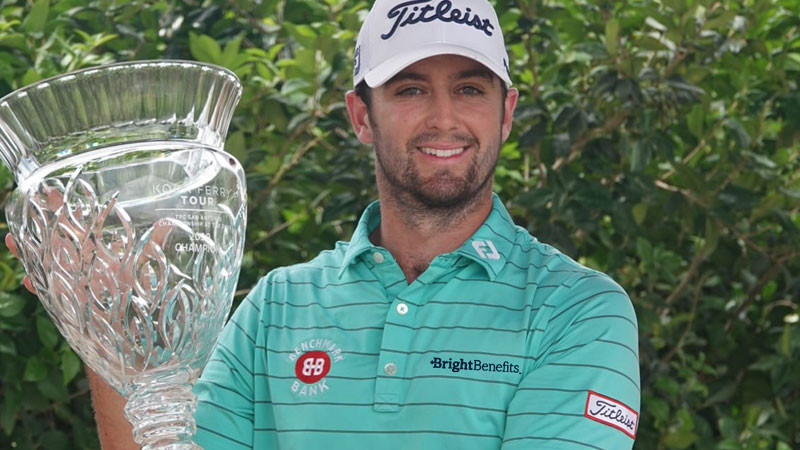 Man holds golf tournament cup after win